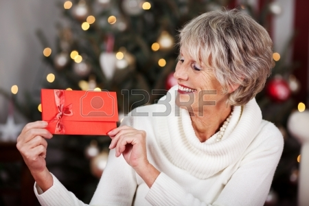 20771779-smiling-stylish-elderly-woman-displaying-a-red-christmas-voucher-in-her-hands-in-front-of-a-twinklin
